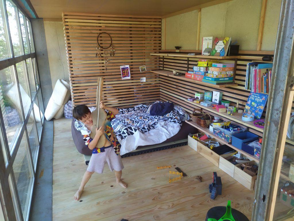 Intérieur aménagé en chambre d'enfant. Étagère de rangement sur la longueur et séparation en fond pour dressing ou salle de bain.