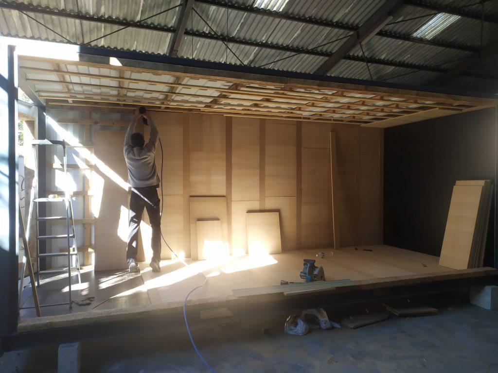 Bardage intérieur et isolation 100% recyclage. Couleur chêne clair sol et murs.